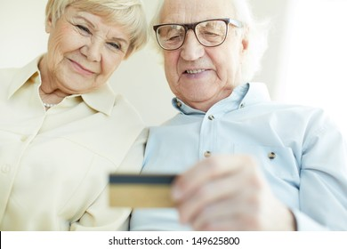 Portrait of elderly man and his wife looking at plastic card