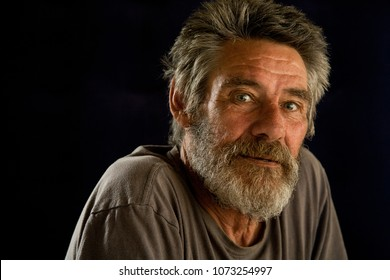 The portrait of an elderly man, hunched shoulders and an untrimmed beard, looking directly at the viewer with the look of having experienced much in his life