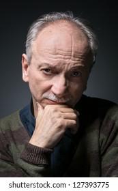 Portrait of an elderly man looks skeptically