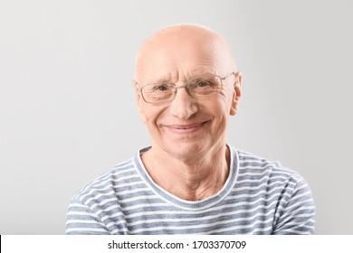 Portrait of elderly man on grey background