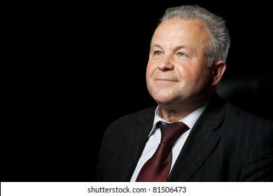 Portrait of the elderly man. A photo against a dark background