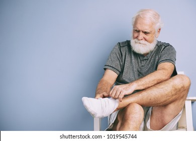 Portrait of elderly man putting on white socks for sports training