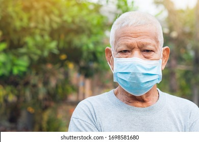 Portrait of elderly man with short white hair, wearing face mask for health because have air pollution PM 2.5. Mask for protect virus, coronavirus, bacteria, pollen grains. Health care concept