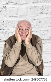 portrait of elderly man in sorrow holding head in hands