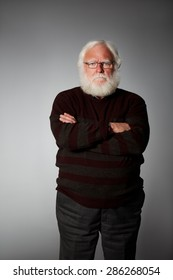 Portrait of elderly man standing with his arms crossed looking at camera seriously against grey background