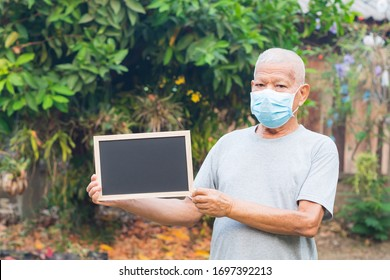 Portrait of elderly man standing holding a black label and wearing face mask for healthy because have air pollution PM 2.5. Mask for protect Virus, Bacteria, Pollen Grains. Healthcare concept
