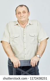 Portrait of elderly man standing propping hands on back of chair.