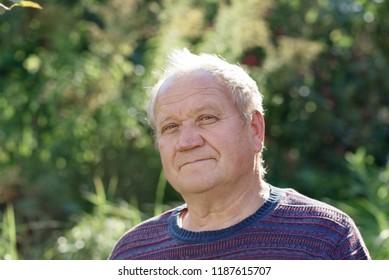 portrait of  elderly man in sunny autumn  park