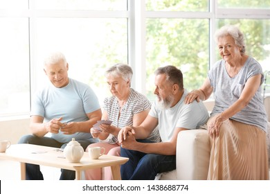 Portrait of elderly people playing cards in nursing home