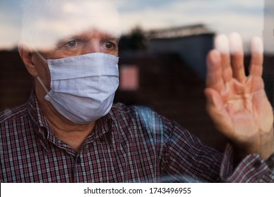 Portrait of elderly senior citizen wearing face mask looking through room window,Coronavirus COVID-19 pandemic outbreak nursing home crisis,high mortality rate and death cases among older population