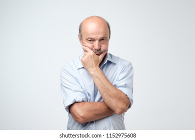 portrait of the elderly serious man rubbing his chin. Mature experienced male trying to solve a problem