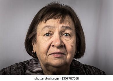 Portrait of an elderly upset woman. Toned.