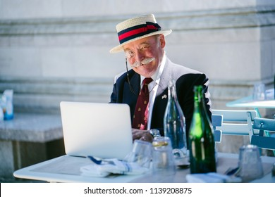 Portrait of an elderly, well-dressed and handsome gentleman sitting in a cafe during the day and working on his laptop computer. He is wearing a two-pieced suit, tie, monocle and hat in summer.