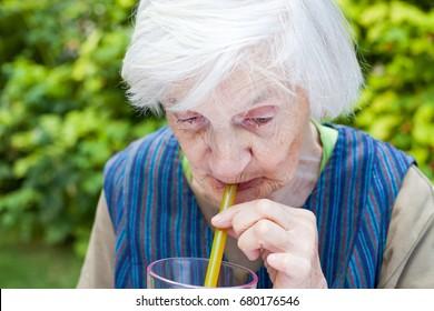 Portrait of an elderly woman with alzheimer disease drinking raspberry juice in the garden