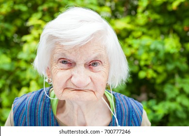 Portrait of an elderly woman with Alzheimer disease listening to music with headphones in the park, outdoor