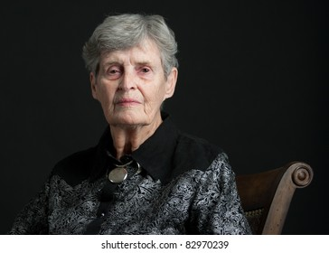A portrait of an elderly woman with a black background