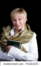 Portrait of an elderly woman with a book in her hands in a white shirt with a shawl on her shoulders against a dark background close-up