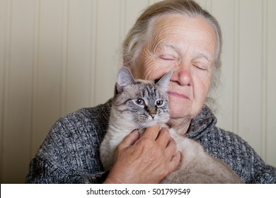 Portrait of an elderly woman with cat on a light background.
