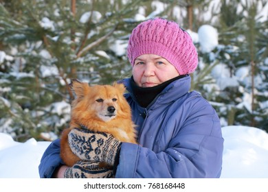 Portrait of an elderly woman with a dog in her arms.