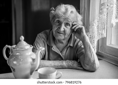 Portrait of elderly woman drinking tea at table.