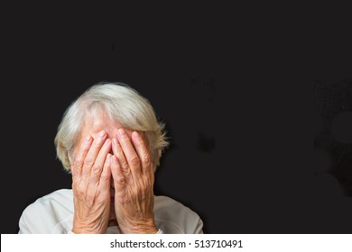 Portrait of an elderly woman with face closed by hands on black