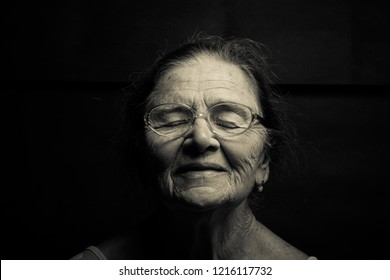 Portrait of an elderly woman with glasses with closed eyes