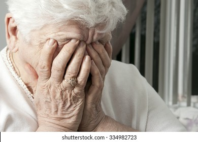 A portrait of an elderly woman having some depress problem. She have the hand on si face.
