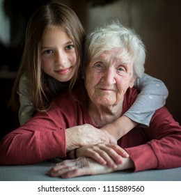 Portrait of an elderly woman with her little granddaughter. Old and young.