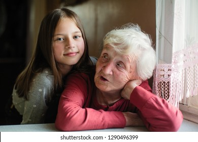Portrait of elderly woman with her little girl granddaughter.