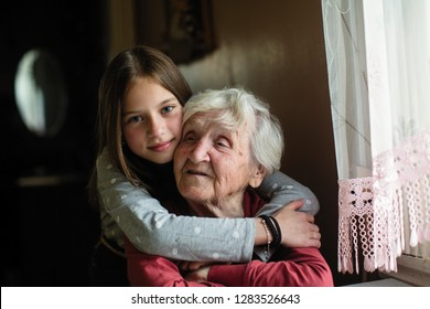 Portrait of an elderly woman with her young granddaughter.