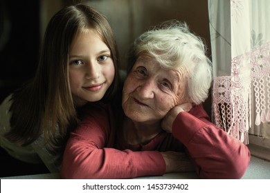Portrait of elderly woman with her young great-granddaughter.