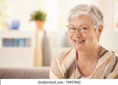 Portrait of elderly woman at home, looking at camera, smiling.?