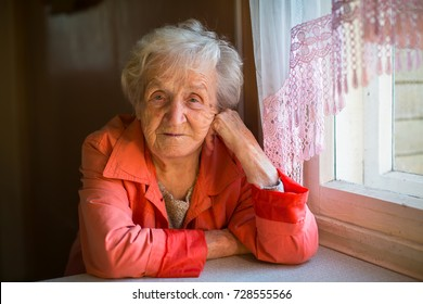 Portrait of an elderly woman in the house near the window.
