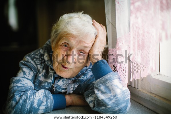 Portrait of elderly woman in the house sitting at the table.