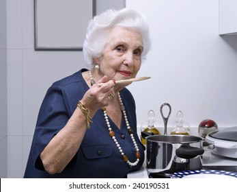 Portrait of an elderly woman in the kitchen, tasting the food