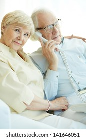 Portrait of elderly woman looking at camera with her husband talking on the phone near by