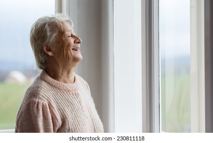 Portrait of Elderly woman looking out window, Grandmother smiling