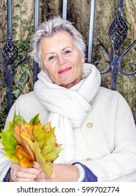 Portrait of elderly woman with maple leaves in autumn park