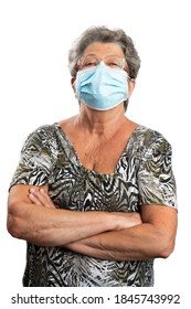 Portrait of elderly woman model standing with arms crossed wearing medical or surgical face mask covering nose and mouth to prevent covid19 influenza virus infection pandemic concept isolated on white