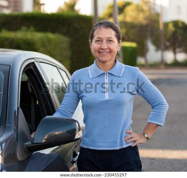 Portrait of  elderly  woman near car.