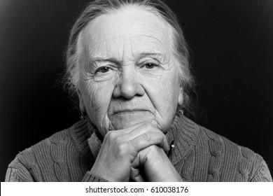 Portrait of elderly woman on dark background. Wistfulness. Toned.