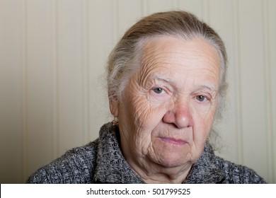 Portrait of an elderly woman on a light background.