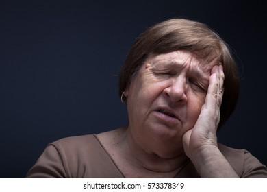 Portrait of elderly woman. Pain.