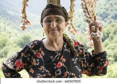 Portrait of an elderly woman picking dried queue garlic in balcony back view, villagers preserving garlic for longer time.