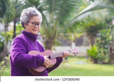 Portrait of elderly woman playing ukulele in her garden. The music and musical instrument makes very happy old woman and good mental health. Health care concept. Space for text