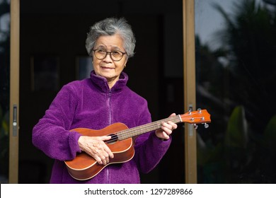 Portrait of elderly woman playing ukulele at home. The music and musical instrument makes very happy old woman and good mental health. Health care concept