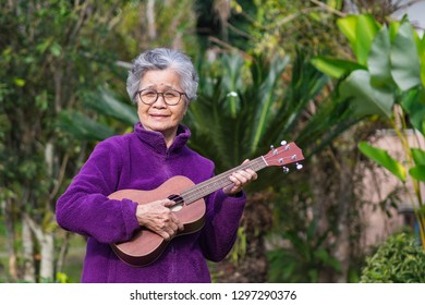 Portrait of elderly woman playing ukulele in her garden. The music and musical instrument makes very happy old woman and good mental health. Health care concept