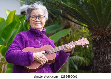 Portrait of elderly woman playing ukulele in her garden. Relaxing by singing and play small guitar happy and enjoy life after retired. People and relaxation concept