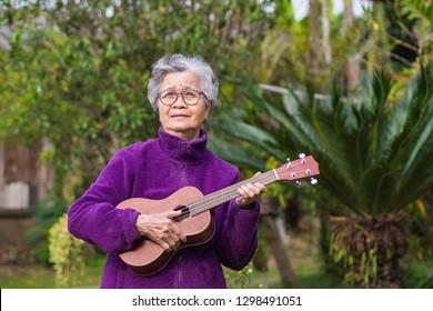 Portrait of elderly woman playing ukulele in her garden.