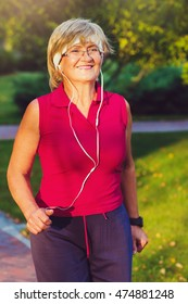 Portrait of elderly woman running with headphones and smartwatches in the park in evening sunset